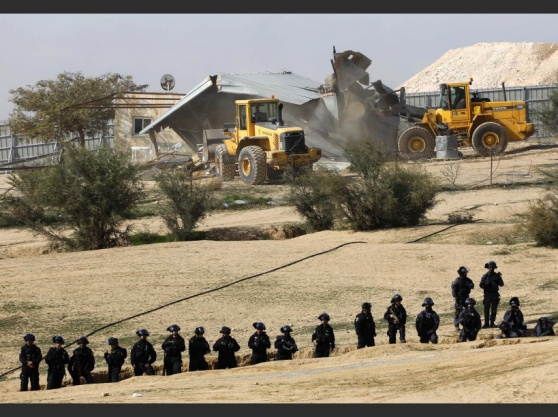 Israeli policemen stand guard as bulldozers demolish homes in the Bedouin village of Umm al-Hiran, which is not recognized by the Israeli government, near the southern city of Beersheba, in the Negev desert, on January 18, 2017. An Israeli policeman was killed while taking part in an operation to demolish homes in the Bedouin village, with authorities claiming he was targeted in a car-ramming attack. The driver was earlier reported shot dead by police as residents disputed the police version of events, saying the driver was heading to the scene to talk with authorities in an attempt to halt the demolitions. / AFP PHOTO / MENAHEM KAHANA